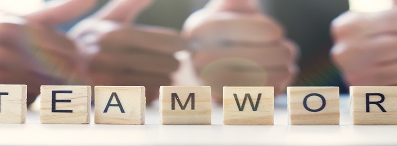 """""""Teamwork"""" word on business working table. Wooden cross word alphabet """"Teamwork"""". Business teamwork concept."""