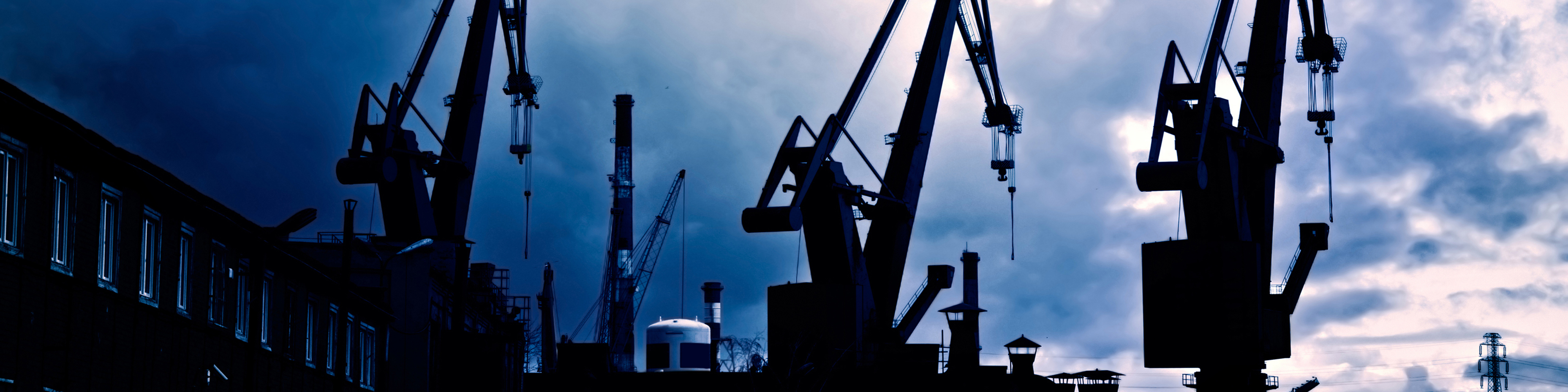 Industrial conceptual image. Dark and sullen clouds over industrial shipyard area with cranes.